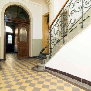gulv af hårdtbrændte keramiske gulvfliser i mønster af gul og grå med bort af brun, grå og sort