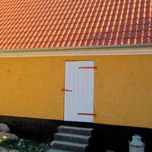 gul pudset bygning malet med kalkmaling
