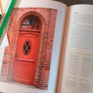 Bog om bygningsbevaring opslået med papir lineal og tush