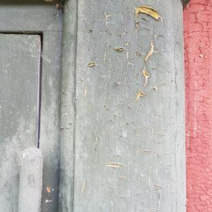 gammel skallende linoliemalet dør i støvet blå med rød karm
