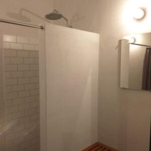 syltetøjsglaslampe i rustikt badeværelse med pudsede vægge